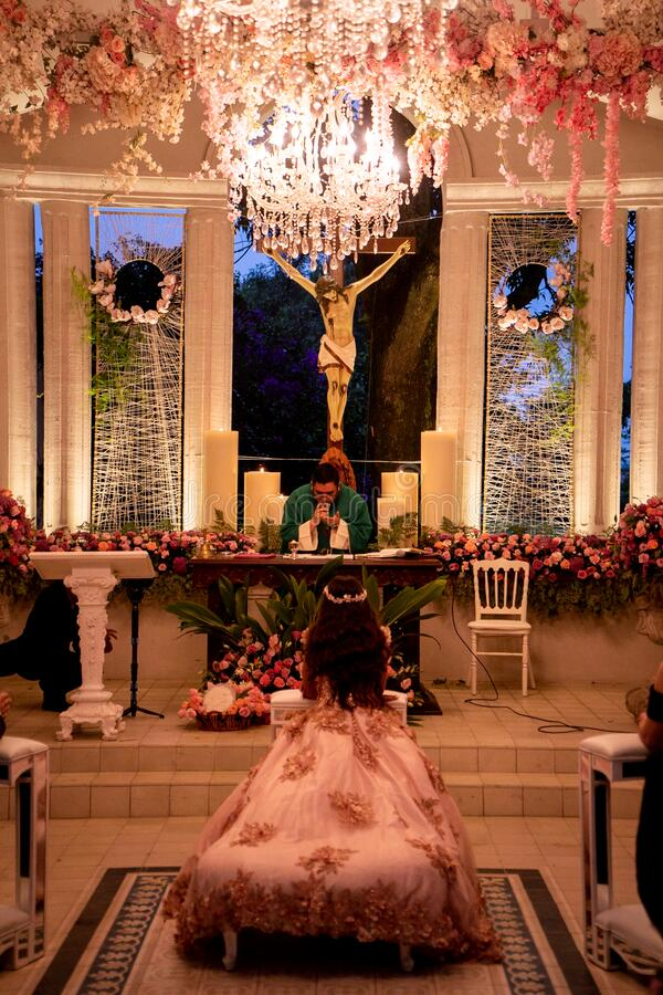 Quinceañera sweet 16 religious ceremony at chappel. Or church, pink decoration and illumination stock image