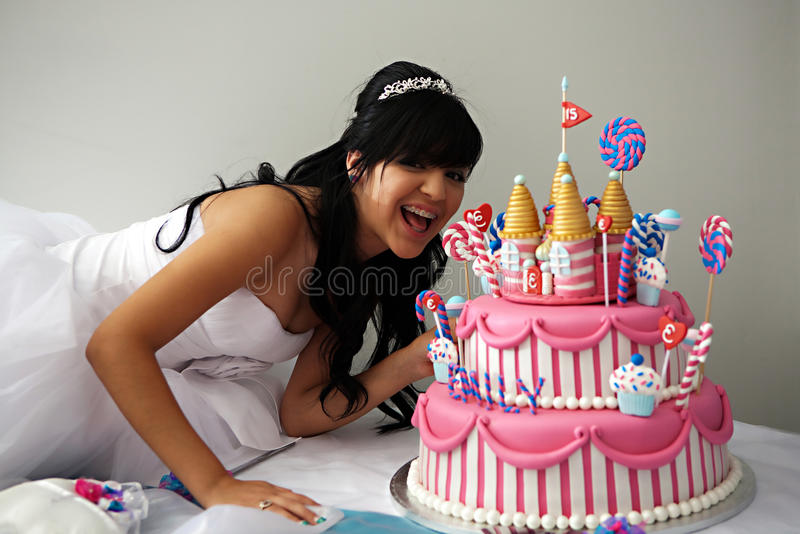 Quinceanera Birthday Cake. A 15 year old hispanic girl celebrates her birthday with a fancy birthday cake with a candyland theme. The three layer cake is covered royalty free stock photography