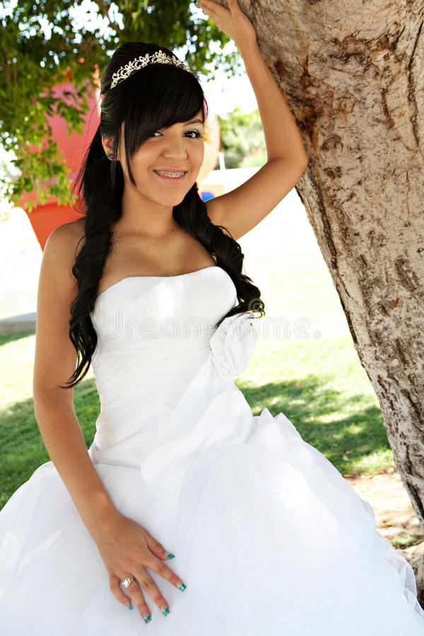 Quinceanera Birthday Girl. A 15 year old hispanic girl celebrates her birthday with a tiara and fancy white dress royalty free stock photo