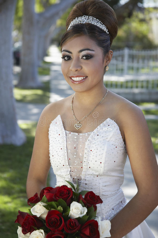 Quinceanera With Flower Bouquet In Lawn. Portrait of a beautiful Quinceanera with flower bouquet in awn stock photography