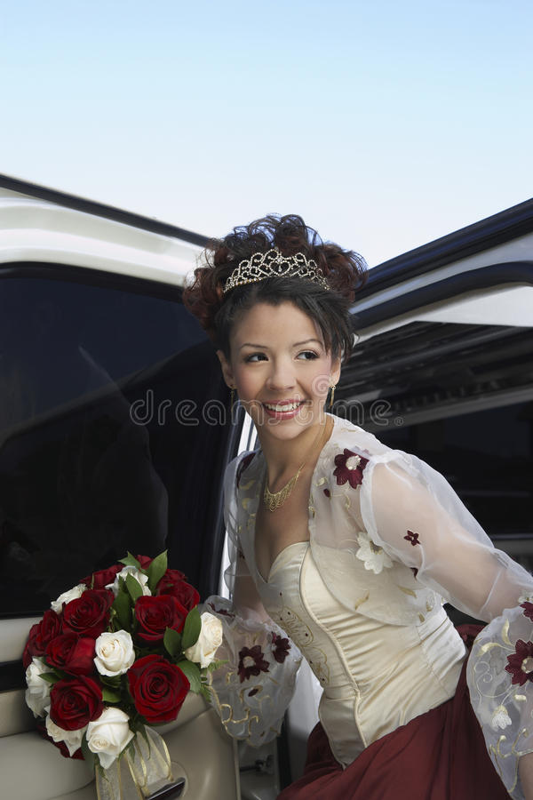 Quinceanera Getting In Car. Happy beautiful Quinceanera getting in the car with rose bouquet royalty free stock photo