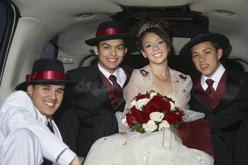Quinceanera Sitting With Three Male Friends In Limousine. Portrait of a beautiful Quinceanera sitting with three male friends in Limousine stock photography
