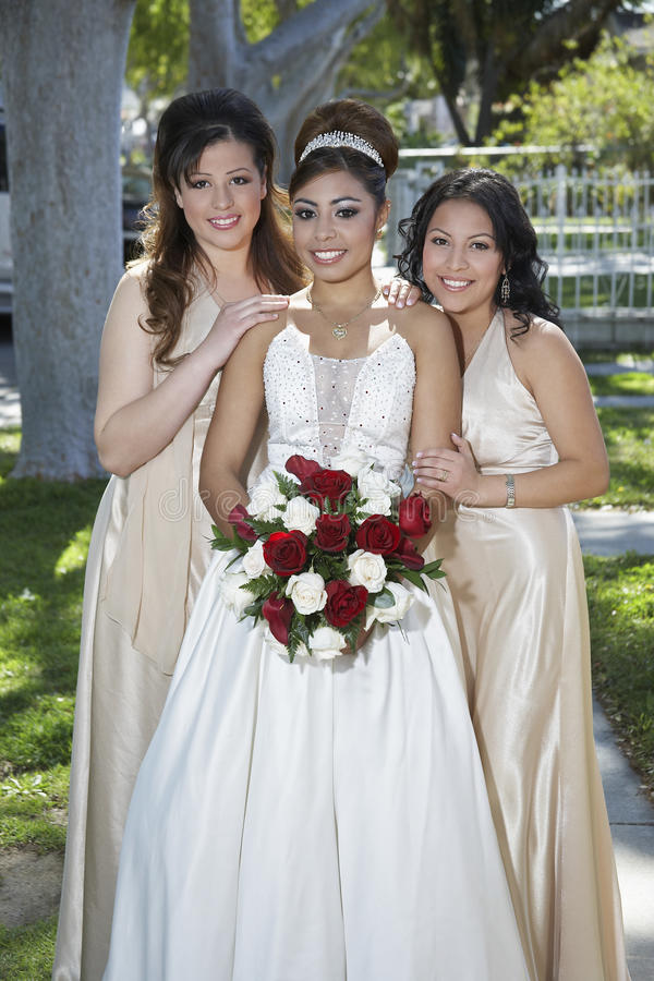 Quinceanera Standing With Female Friends. Portrait of a beautiful Quinceanera holding flowers standing with female friends in lawn stock images