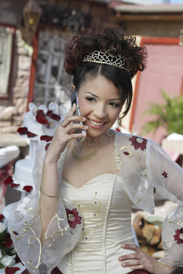 Quinceanera Using Cell Phone. Cheerful girl in Quinceanera dress using cell phone with hand on hip royalty free stock photos