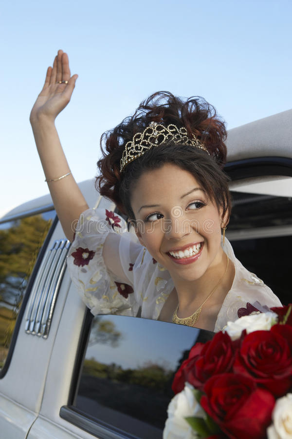 Quinceanera Waving Hand From Car Window. Happy beautiful Quinceanera waving hand from car window stock photo