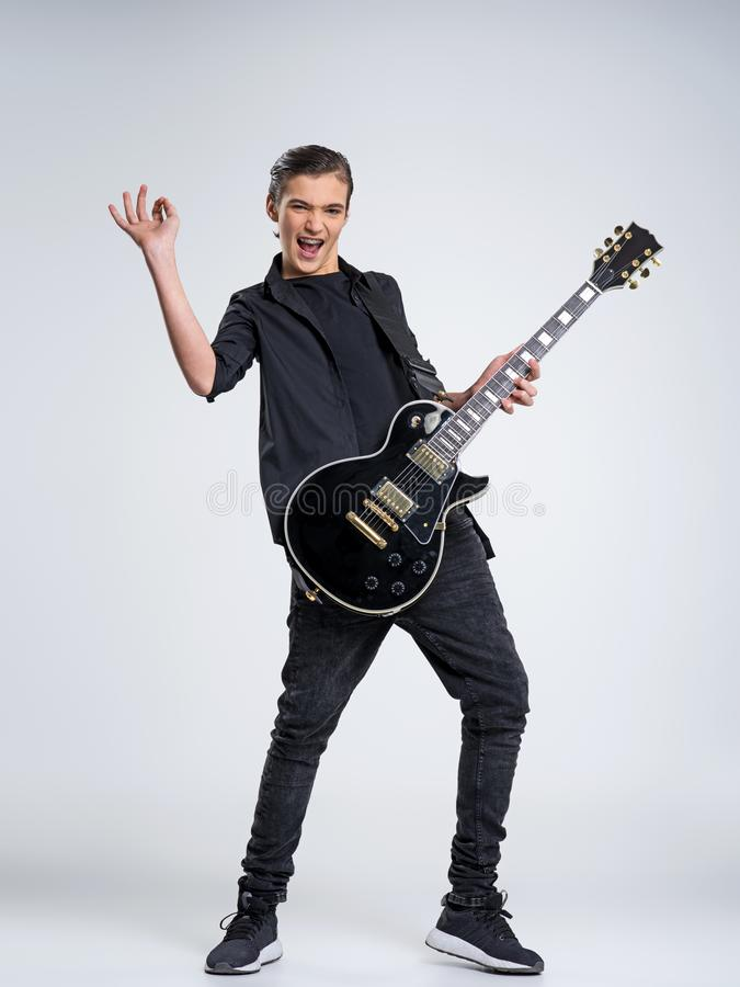Quindici anni del chitarrista con una chitarra elettrica nera Il musicista adolescente tiene la chitarra immagine stock libera da diritti