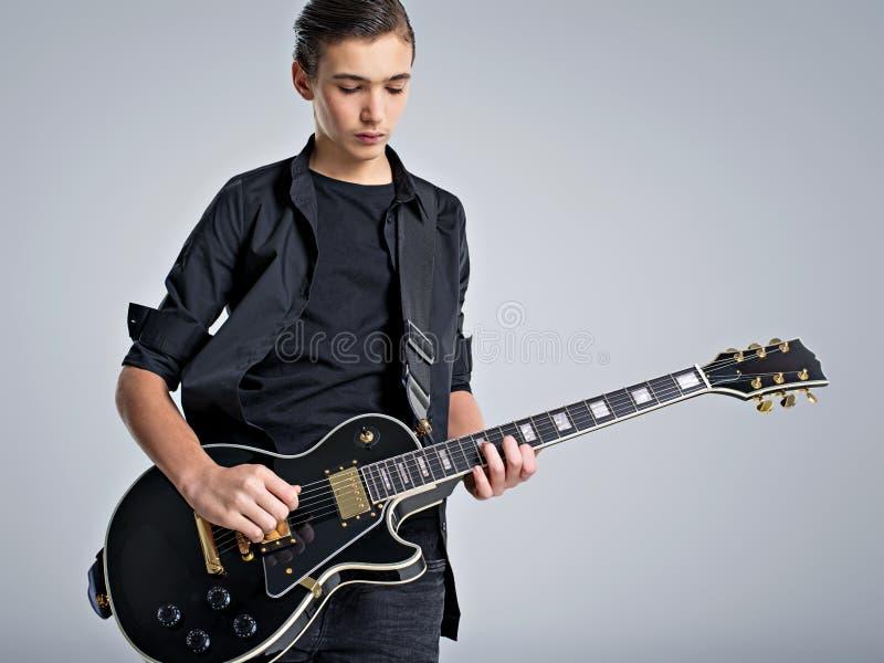 Quindici anni del chitarrista con una chitarra elettrica nera Il musicista adolescente tiene la chitarra immagini stock