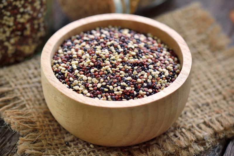Quinoa σπόροι στο κύπελλο στο ξύλο στοκ εικόνες