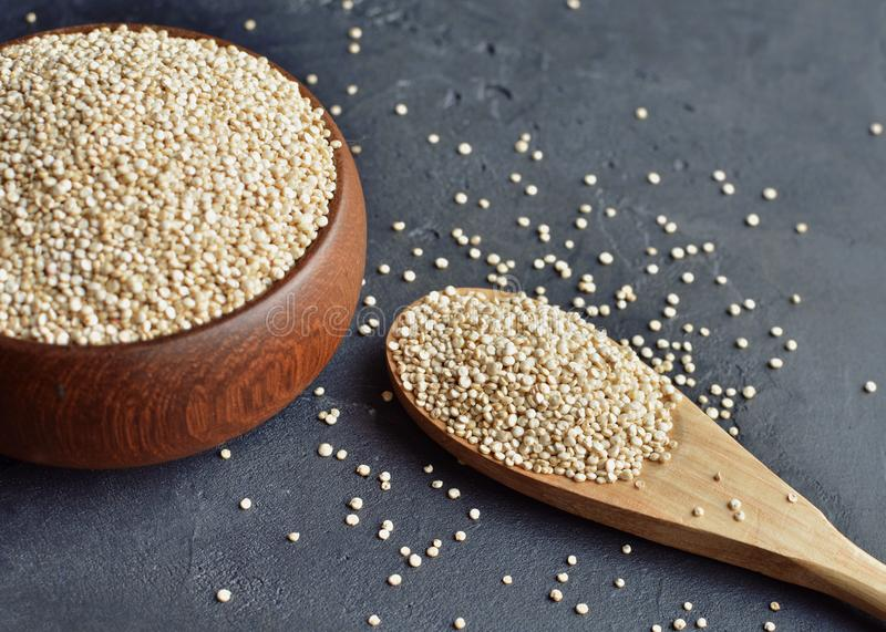 Quinoa in a brown wooden bowl and spoon on dark stone background. Dry uncooked cereal grains, cooking ingredient. Organic quinoa in a brown wooden bowl and spoon stock photography