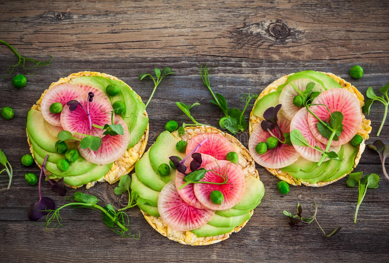Quinoa cakes with vegetables. Organic quinoa cakes with avocado and watermelon radish for breakfast stock images