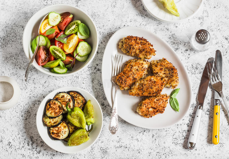 Quinoa crusted chicken, vegetable salad, grill eggplant and pepper - dinner table. On a light background royalty free stock photos