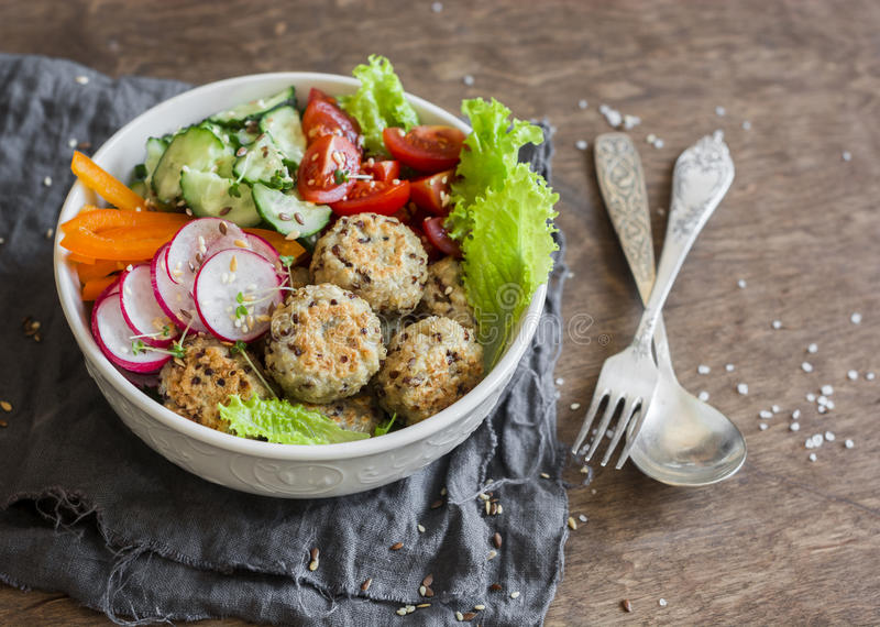 Quinoa meatballs and vegetable salad. Buddha bowl on a wooden table, top view. Healthy, diet, vegetarian food concept. Flat lay royalty free stock images