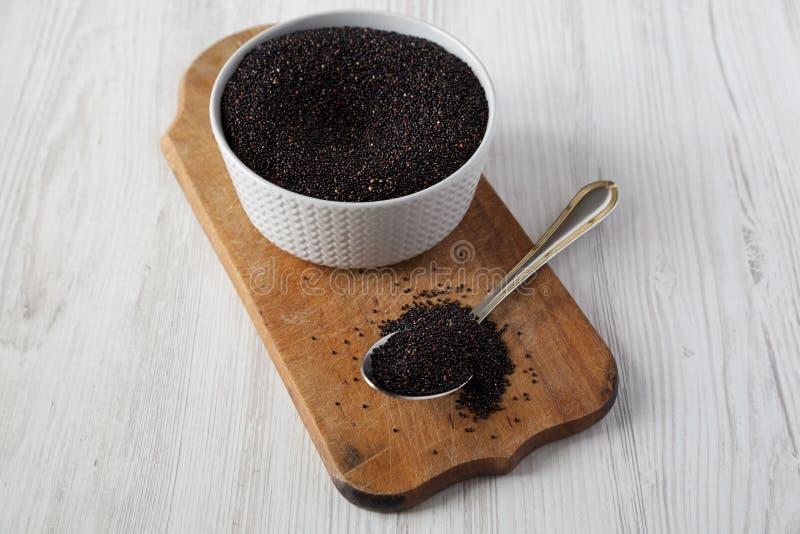 Quinoa negra org?nica cruda libre del gluten en el tablero de madera r?stico sobre la superficie de madera blanca, opini?n de ?ng foto de archivo libre de regalías
