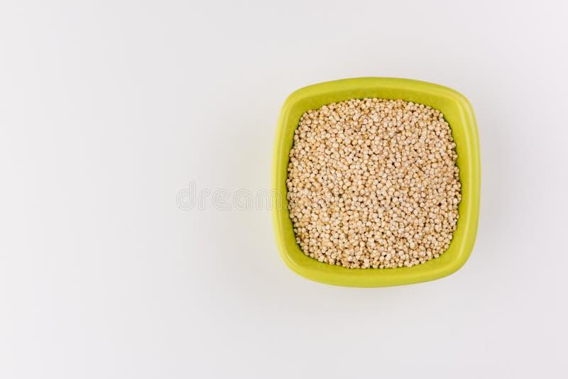 Quinoa no copo cerâmico no fundo branco imagem de stock