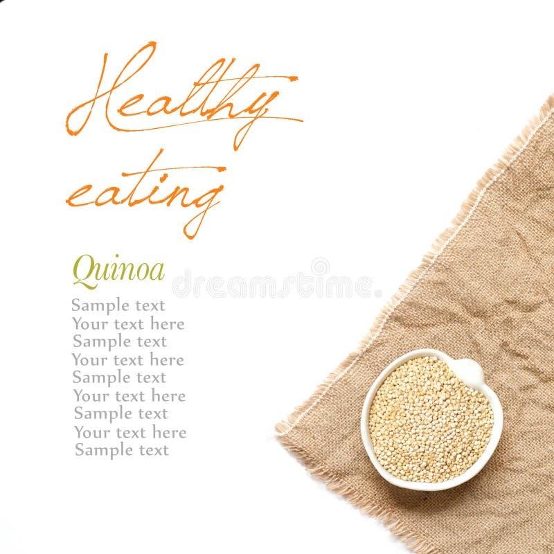 Quinoa organica cruda in una ciotola su un fondo bianco fotografia stock