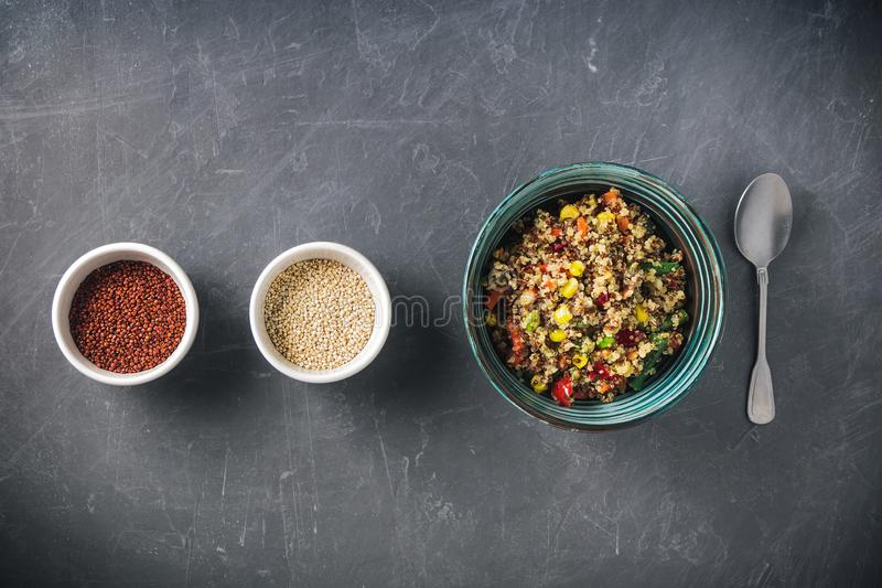 Quinoa salad bowl with colorful vegetables: green beans, carrot, corn, bell pepper, peas and two cups with red and white quinoa se stock photo