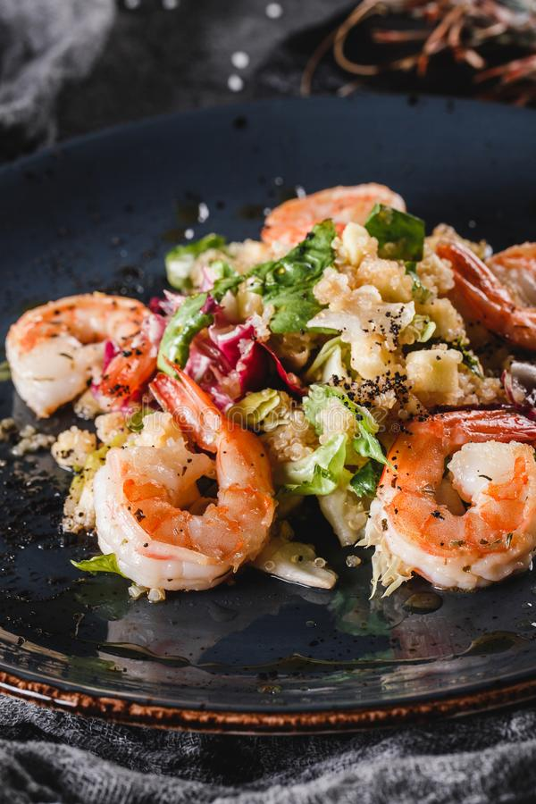Quinoa salad with shrimp and mixed greens in bowls over grey background. Healthy food, clean eating, dieting, top view stock image