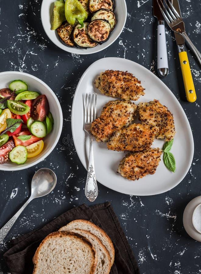 Quinoa täckt med en skorpa höna, grönsaksallad, grillad aubergine och peppar - matställetabell På en mörk bakgrund royaltyfri foto