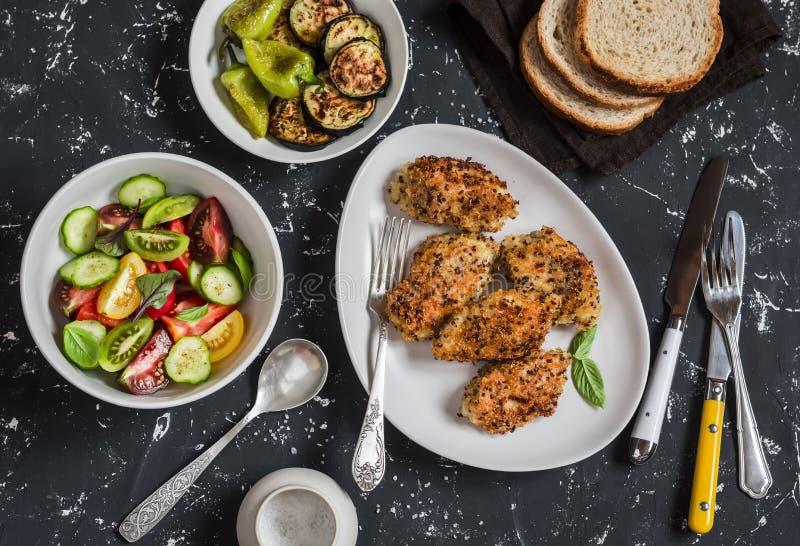 Quinoa täckt med en skorpa höna, grönsaksallad, grillad aubergine och peppar - matställetabell På en mörk bakgrund arkivbilder