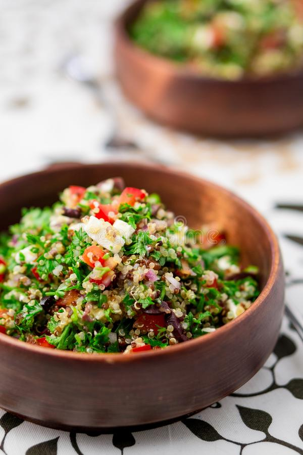 Quinoa tabbouleh salad bowl. This healthy dish mixes tabbouleh & greek style salads, using fresh parsley herb, olives, onions, feta and replacing the bulgur stock photos