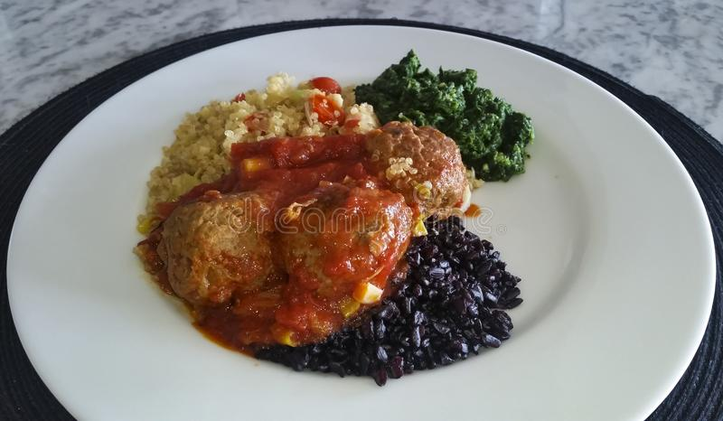 Quinoa, vleesballetjes, zwarte rijst en spinazie, gezond voedsel stock fotografie