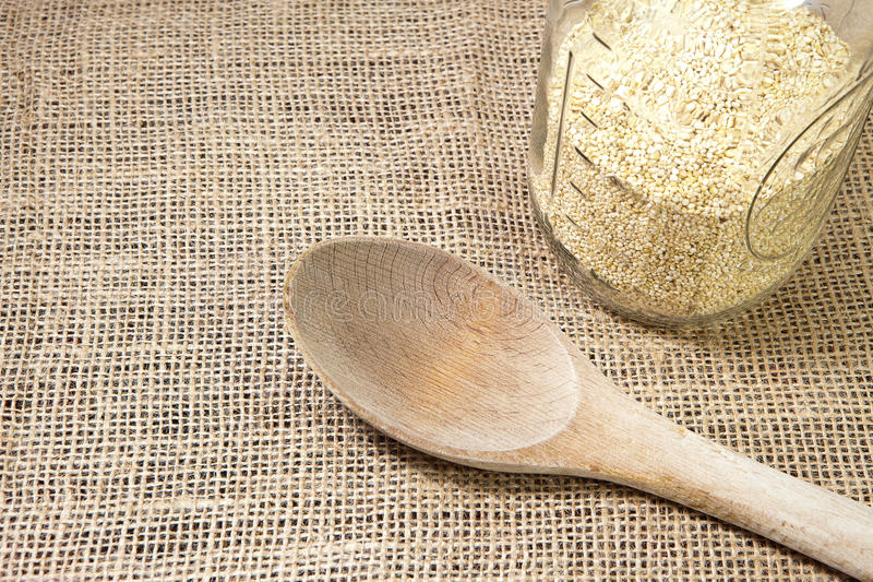 Quinoa and wooden spoon with burlap background-con stock photos