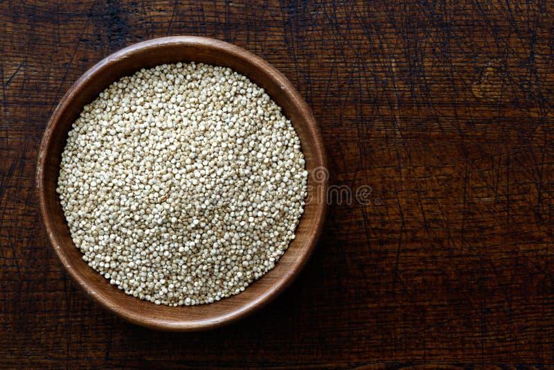 Quinoa zaden in donkere houten die kom op donker bruin hout wordt geïsoleerd voor royalty-vrije stock afbeeldingen