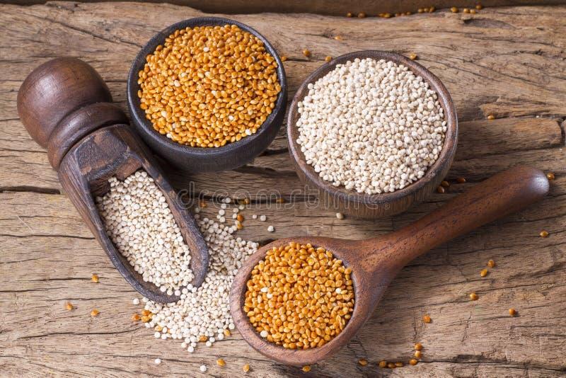 Quinoa zaden en rode gierst in kom op rustiek hout royalty-vrije stock afbeelding