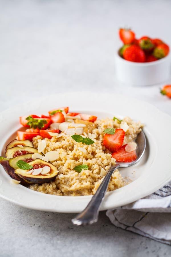 Quinoafrukosthavregröt med jordgubbar och fikonträd i den vita plattan sunt frukostbegrepp royaltyfria foton