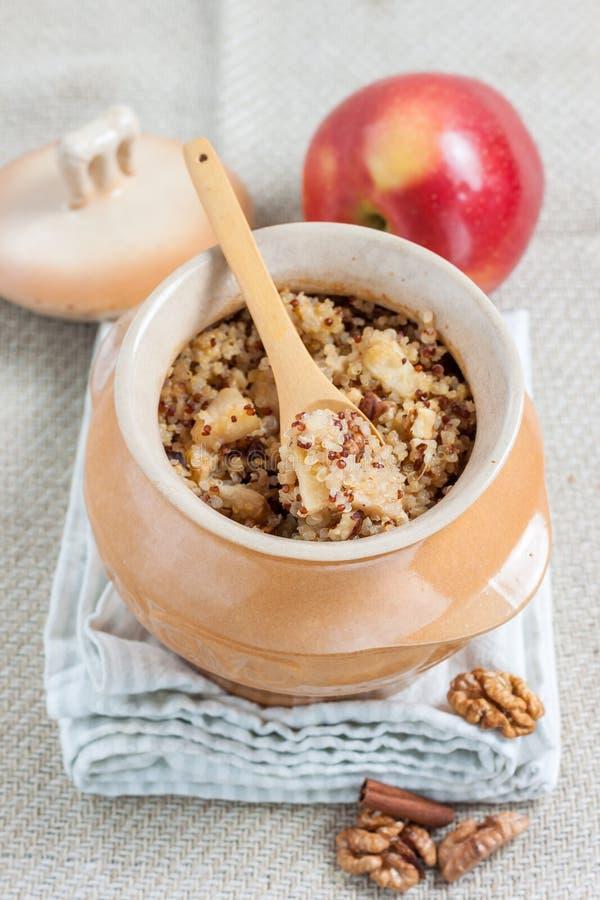Quinoahavregröt med äpplen och valnötter arkivbild