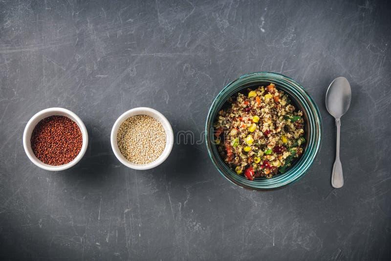 Quinoasalatschüssel mit buntem Gemüse: grüne Bohnen, Karotte, Mais, grüner Pfeffer, Erbsen und zwei Schalen mit rotem und weißem  stockfoto