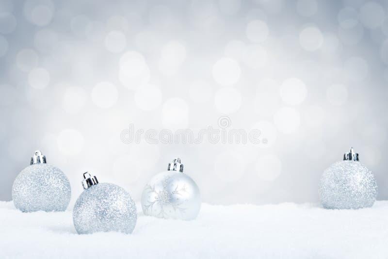 Quinquilharias de prata do Natal na neve com imagem de stock