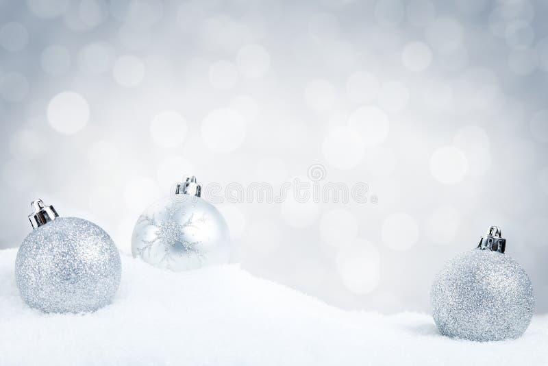 Quinquilharias de prata do Natal na neve com um fundo de prata fotos de stock royalty free