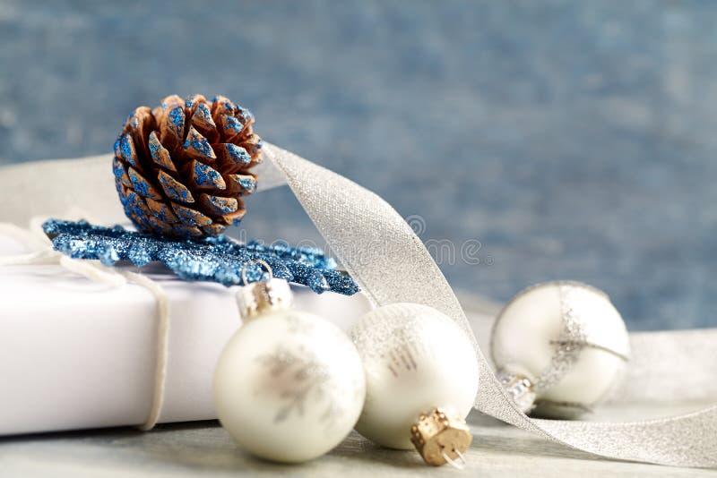 Quinquilharias de prata do Natal, presente branco e fita do cetim foto de stock
