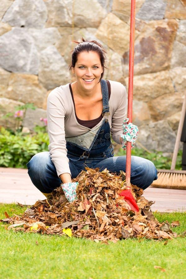 Quintal varrendo da pilha do outono das folhas da mulher alegre imagens de stock royalty free