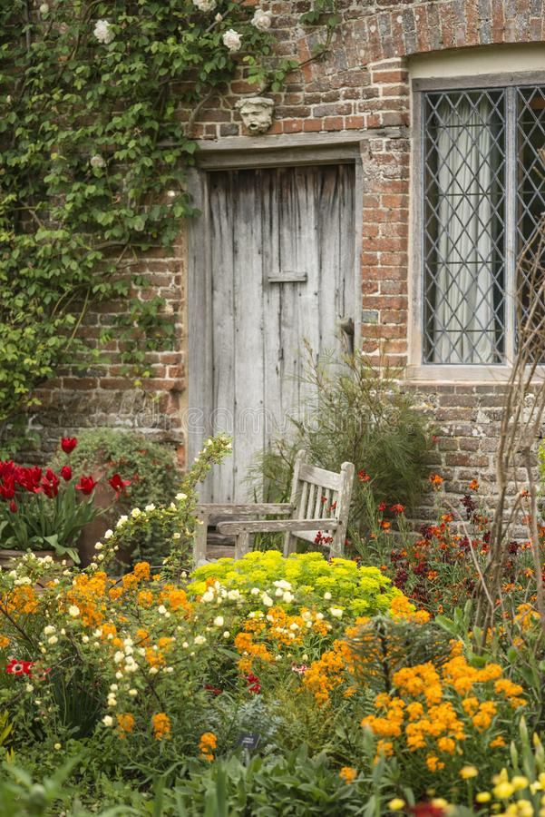 Quintessential vibrant English country garden scene landscape wi. Quintessential English country garden scene landscape with fresh Spring flowers in cottage stock photography