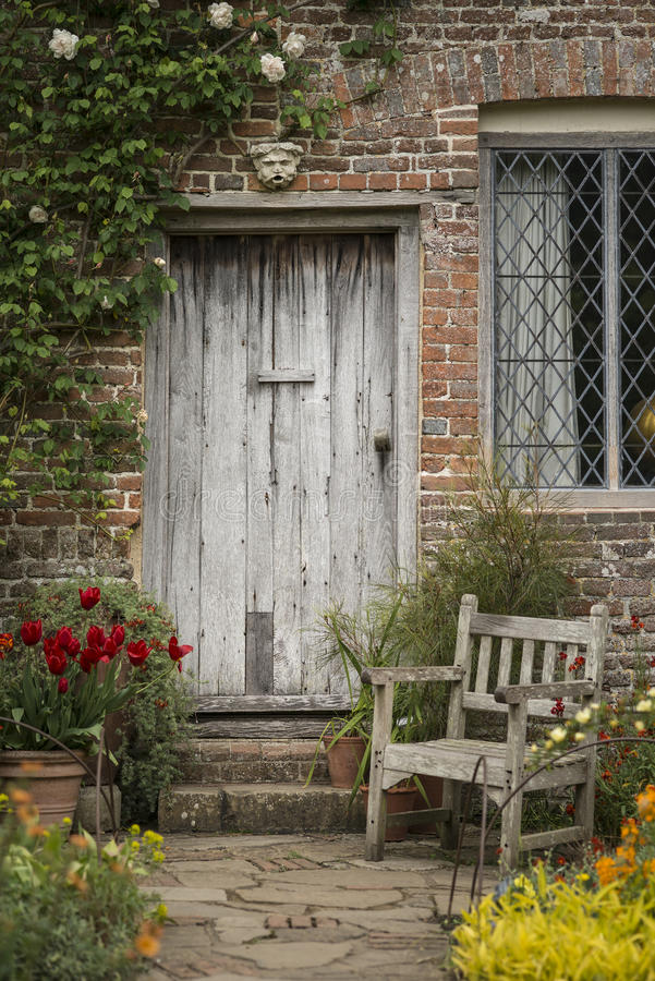 Quintessential old English country garden image of wooden chair. Beautiful quintessential old English country garden image of wooden chair next to vintage back royalty free stock photos