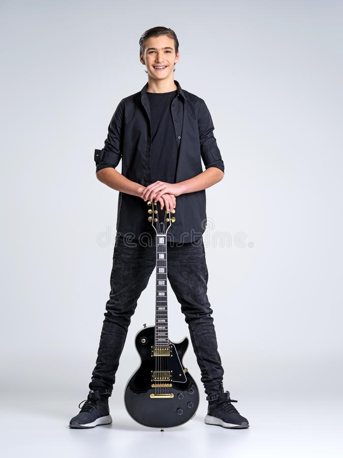 Quinze anos de guitarrista idoso com uma guitarra elétrica preta imagens de stock