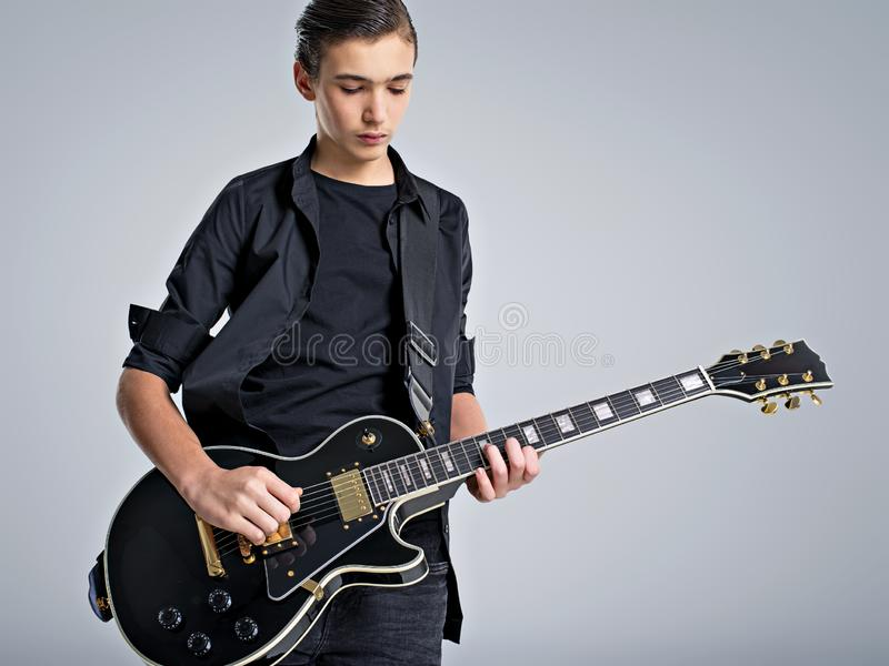 Quinze anos de guitarrista idoso com uma guitarra elétrica preta O músico adolescente guarda a guitarra imagens de stock