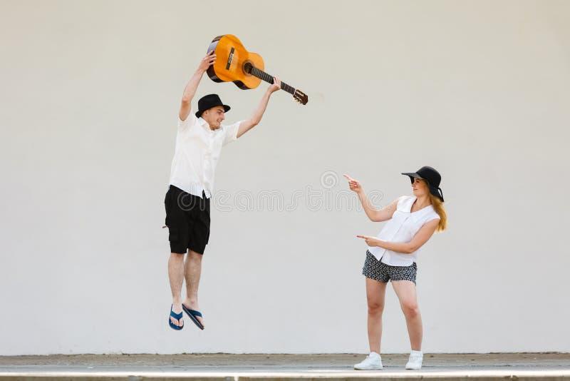 ?quipez sauter avec la guitare, femme se dirigeant ? lui photographie stock