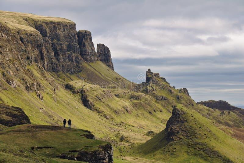 Quiraing, île de Skye, Ecosse - paysage rocheux bizarre avec deux chiffres humains se tenant sur une falaise dans le premier plan images libres de droits