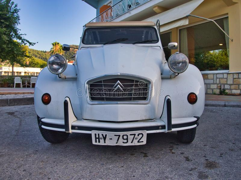 Vintage Citroen 2CV Car Parked on Side of Road. A quirky eccentric white vintage Citroen 2CV, deux chevaux, car parked on road outside workplace royalty free stock photos