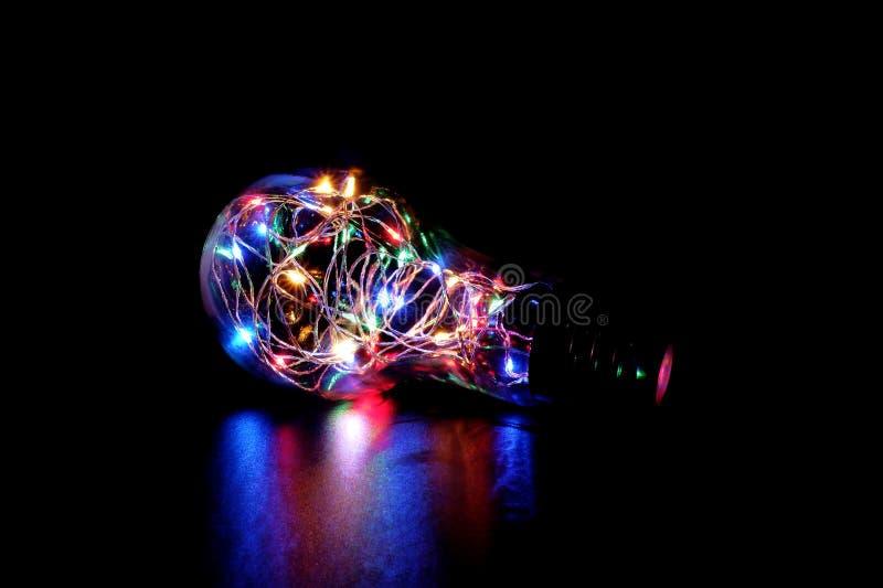 Quirlande électrique colorée dans un pot en verre formé d'ampoule image libre de droits