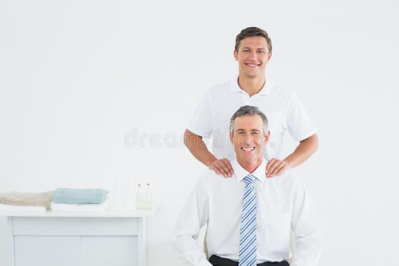 Quiroprático masculino e paciente maduro bem vestido fotografia de stock royalty free