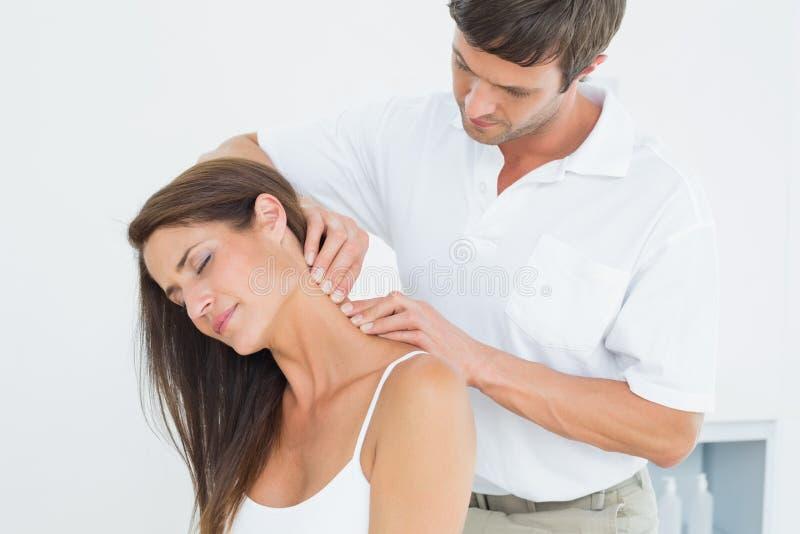 Quiroprático masculino que faz massagens o pescoço de uma jovem mulher imagens de stock royalty free