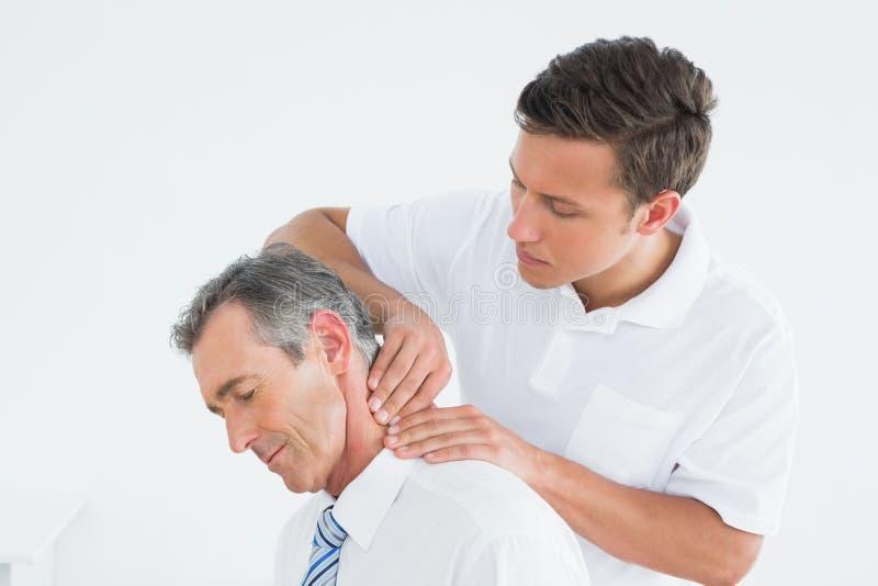 Quiroprático masculino que faz massagens o pescoço dos pacientes imagens de stock royalty free
