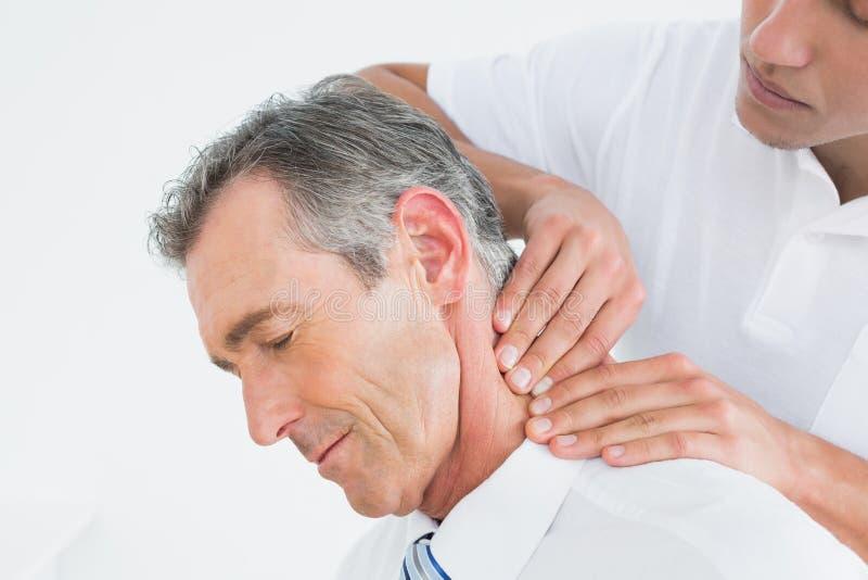 Quiroprático masculino que faz massagens o pescoço dos pacientes fotos de stock royalty free