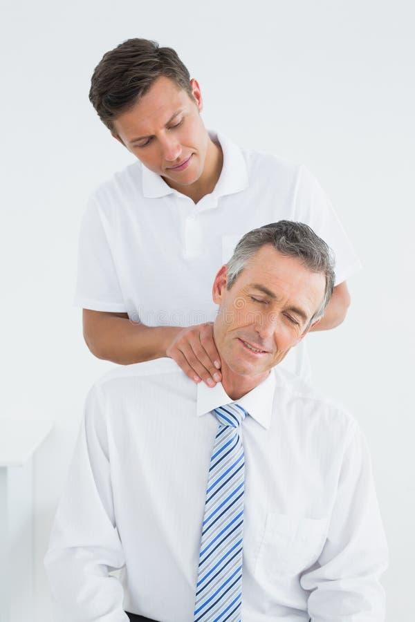Quiroprático masculino que faz massagens o pescoço dos pacientes foto de stock royalty free