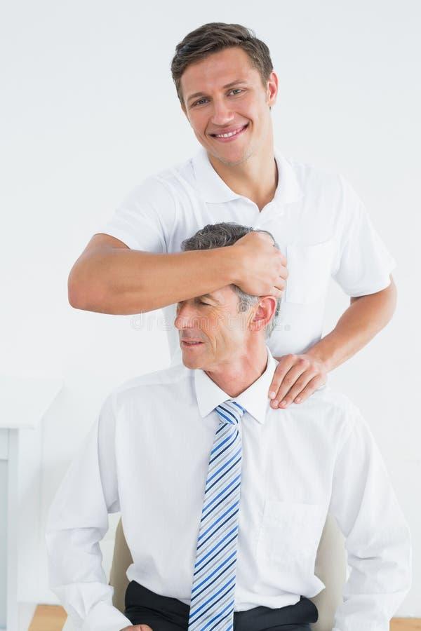 Quiroprático masculino que faz o ajuste do pescoço imagens de stock royalty free