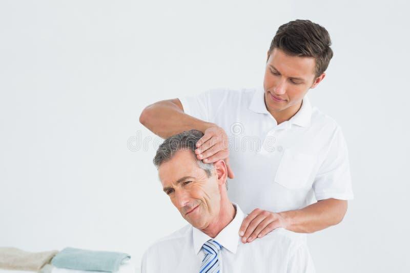 Quiroprático masculino que faz o ajuste do pescoço foto de stock royalty free